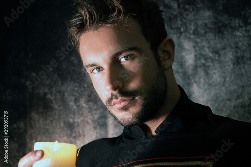 Portrait of handsome medieval knight with beard and blue eyes, holding a candle Wallpaper Mural