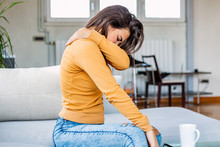 Pain In Her Shoulder. Upper Arm Pain, People With Body-muscles Problem, Healthcare And Medicine Concept. Attractive Young Woman Sitting On The Bed And Holding Painful Shoulder With Another Hand.