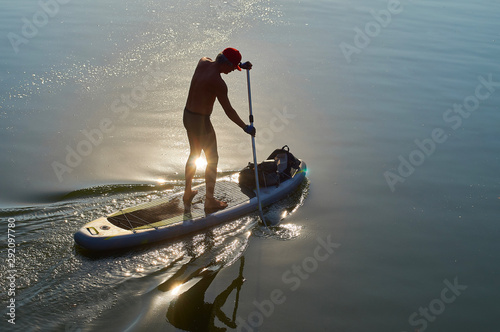 young man spends an active vacation on a beautiful small river at SUP (stand up paddle) - 292097780