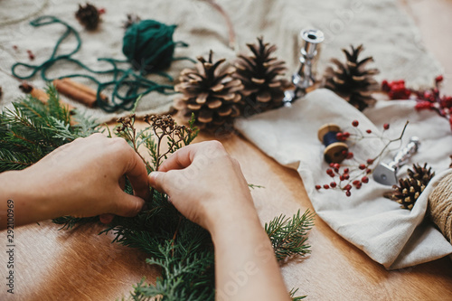 Fototapeta Making rustic Christmas wreath. Hands holding herbs and  fir branches, pine cones, thread, berries, cinnamon on wooden table. Christmas wreath workshop. Authentic stylish still life. obraz
