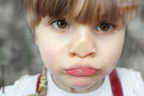 Obraz na plátně Trauriges Mädchen drückt Nase an Fensterscheibe platt