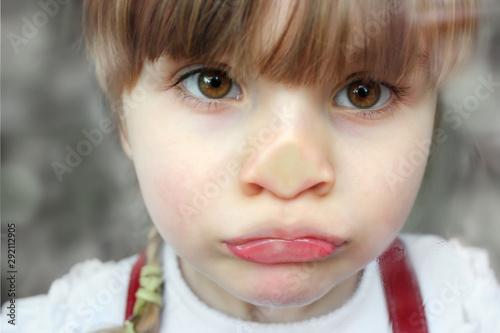 Valokuva Trauriges Mädchen drückt Nase an Fensterscheibe platt