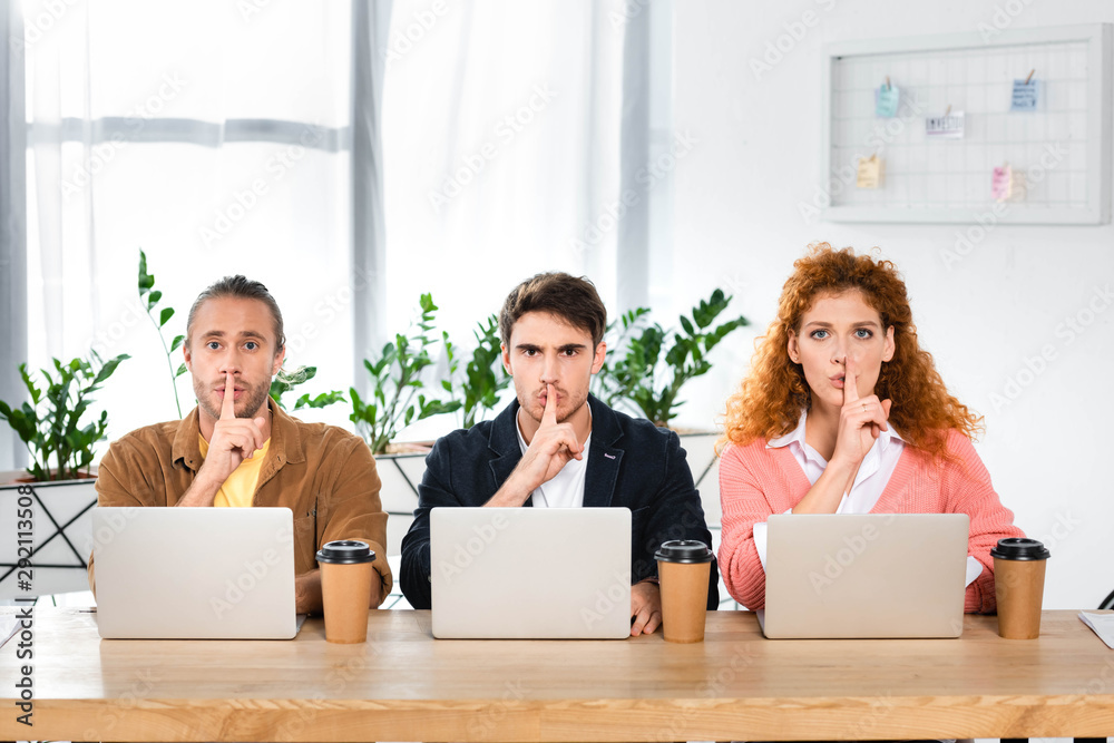 Fototapeta three friends sitting at table and showing shh gestures in office