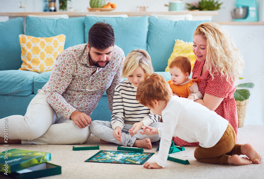 Fototapeta happy family playing board games together at home