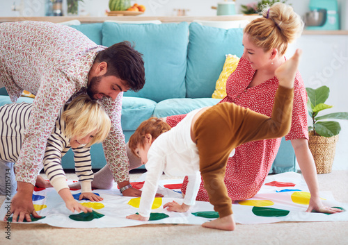 Obraz happy family having fun together, playing twister game at home - fototapety do salonu