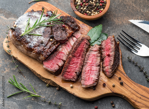 Medium rare Ribeye steak with herbs and a piece of butter on the wooden tray.