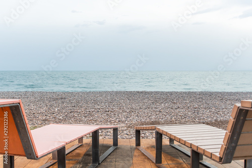 Fotografia  Low angle view of deck chairs on a pebble beach