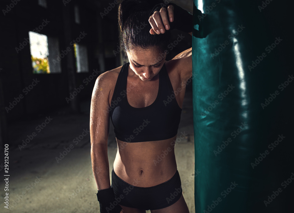 Fototapeta Female boxer resting after punching a boxing bag in warehouse.