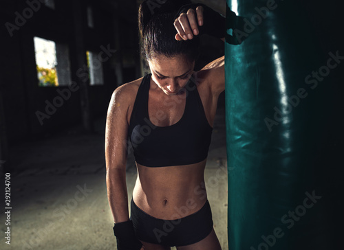 Female boxer resting after punching a boxing bag in warehouse. Canvas Print