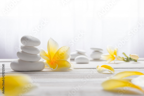 Fotografia  Stacked white stones on white background with yellow frangapani flower - Lifestyle and alternative health concept image with copy space for text