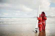Two Surfers Dressed As Santa C...