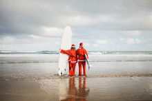 Two Surfers Dressed As Santa C...