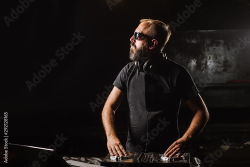 DJ plays on a mixer in the club on black background - 292128165