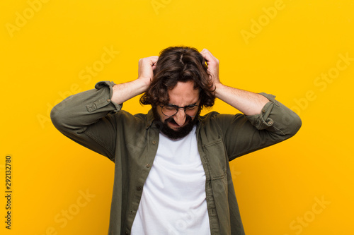 Obraz na plátně  young crazy man feeling stressed and frustrated, raising hands to head, feeling