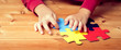 canvas print picture - Banner picture of an autistic child's hands playing a puzzle symbol of Public awareness for autism spectrum disorder. World Autism Awareness day April 2, Supportive, Understanding and Acceptance.
