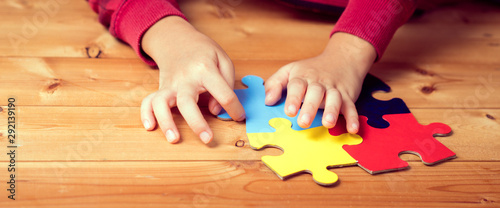 Banner picture of an autistic child's hands playing a puzzle symbol of Public awareness for autism spectrum disorder Canvas Print