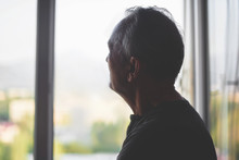 Silhouette Of An Elderly Man On A Window Background. Old Age. Depression Pensioner. Retirement Loneliness.