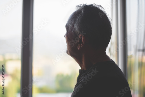 Silhouette of an elderly man on a window background Canvas Print