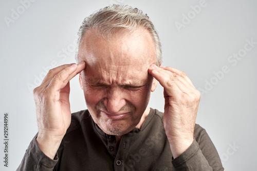 Fotografia An old man touches his head. Headache. Alzheimer's disease