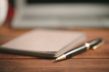 Close Up Of An Open Notepad With Pen On Wooden Table
