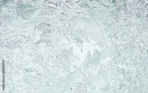 beautiful festive frosty pattern with white snowflakes on a blue background on g Fototapet