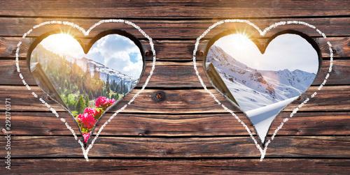 fototapeta na lodówkę Sommer und Winter Ausblick durch ein Herzfenster auf einer Alm