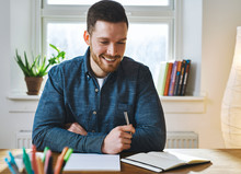 Happy Young Bearded Man Looking At Notebook