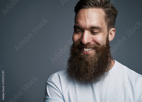 Fotografie, Obraz Smiling bearded hipster standing against a gray background