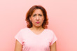 canvas print picture middle age woman feeling sad and whiney with an unhappy look, crying with a negative and frustrated attitude against pink wall