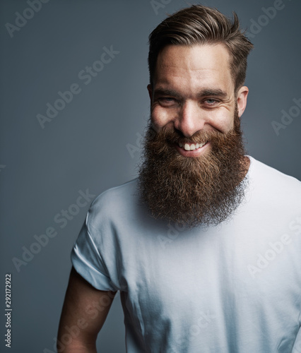 Obraz Bearded young man laughing against a gray background - fototapety do salonu