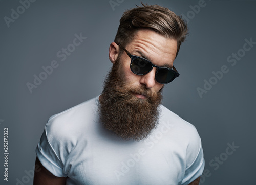 Canvas Print Stylish young hipster with a long beard wearing sunglasses