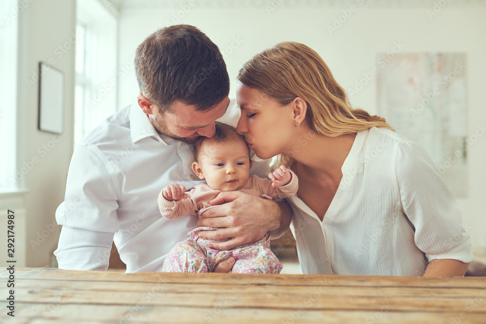 Fototapety, obrazy: Mother kissing her little girl cradled in her husband's arms