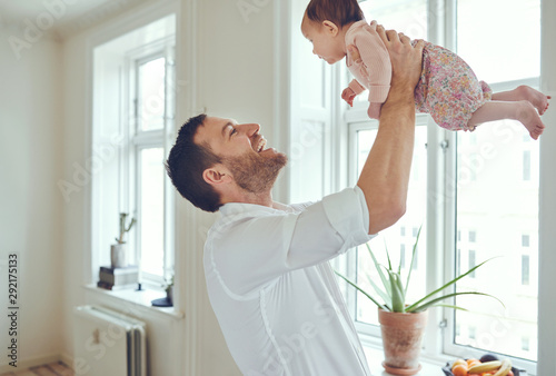 Vászonkép  Loving father holding his baby girl up in the air
