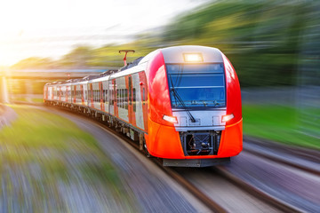 Passenger electric train rides at high speed on the turn of the railway line.