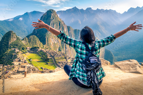 A woman tourist contemplating the amazing landscape of Machu Picchu with arms open Canvas Print