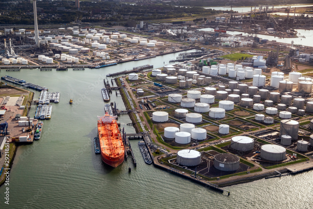 Fototapeta Aerial view of a large orange oil tanker moored at an oil storage silo terminal in an industrial port.