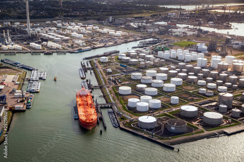 Photo Aerial view of a large orange oil tanker moored at an oil storage silo terminal in an industrial port