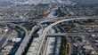 4K. Aerial observation of the crossing multi-level roadbed of Los Angeles freeway. Famous view. Daytime panorama of the overpass, moving cars and buildings.