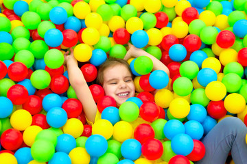 Fototapeta na wymiar Funny child girl having fun in ball pit with colorful balls.