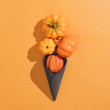 Leinwanddruck Bild - Icecream made with black ice-cream cone and pumpkins on orange background. Halloween sweet dessert. Flat lay minimal concept.