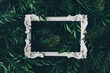 Leinwanddruck Bild Creative winter layout made of branches and leaves with white decorative frame. Flat lay. Nature concept