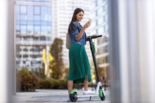 Young Woman With Electric Scooter Checking Her Smartphone