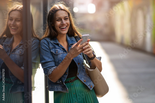 obraz PCV Young woman with smartphone in an urban city area