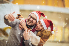 Young Beautiful Couple With Santa Hats Make Selfie Photo In The City.