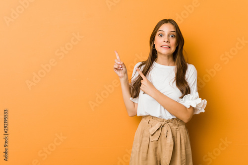 Fototapeta Young caucasian woman shocked pointing with index fingers to a copy space