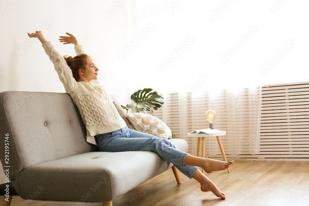 Fototapeta Young beautiful woman wearing white sweater on grey textile sofa at home. Attractive slim female in domestic situation, resting on couch in her lofty apartment. Background, copy space, close up.