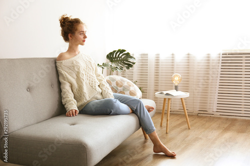 Young beautiful woman wearing white sweater on grey textile sofa at home Billede på lærred