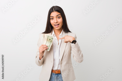 Cuadros en Lienzo Young arab business woman holding dollars surprised pointing at himself, smiling broadly