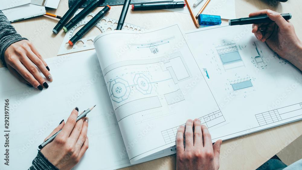 Fototapeta Interior design. Architect teamwork. Creative engineers working on project with scheme.