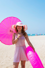 Beautiful Woman In Pink Dress Walking On Sand Beach Wearing A Hat And Holding An Umbrella And A Floater